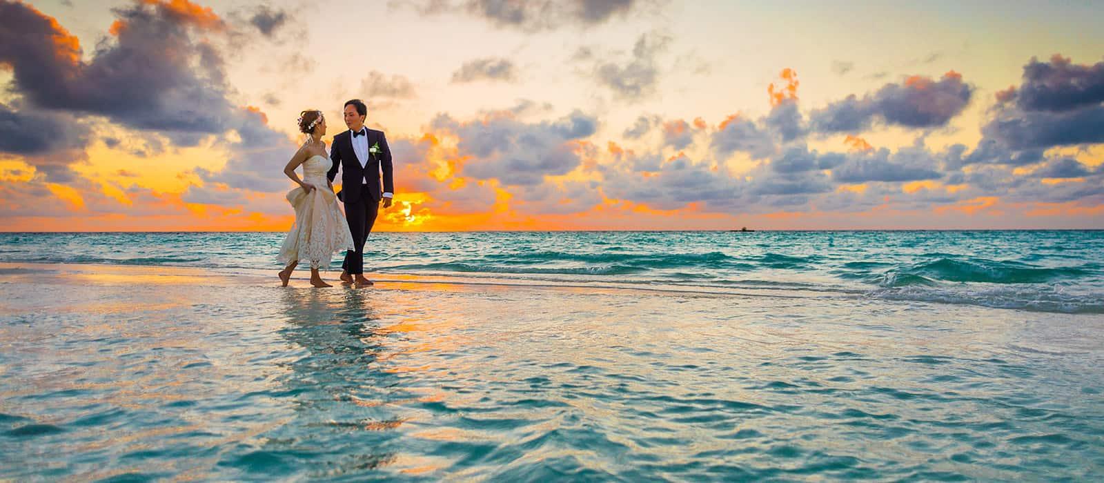Pareja de recien casados caminando por la orilla